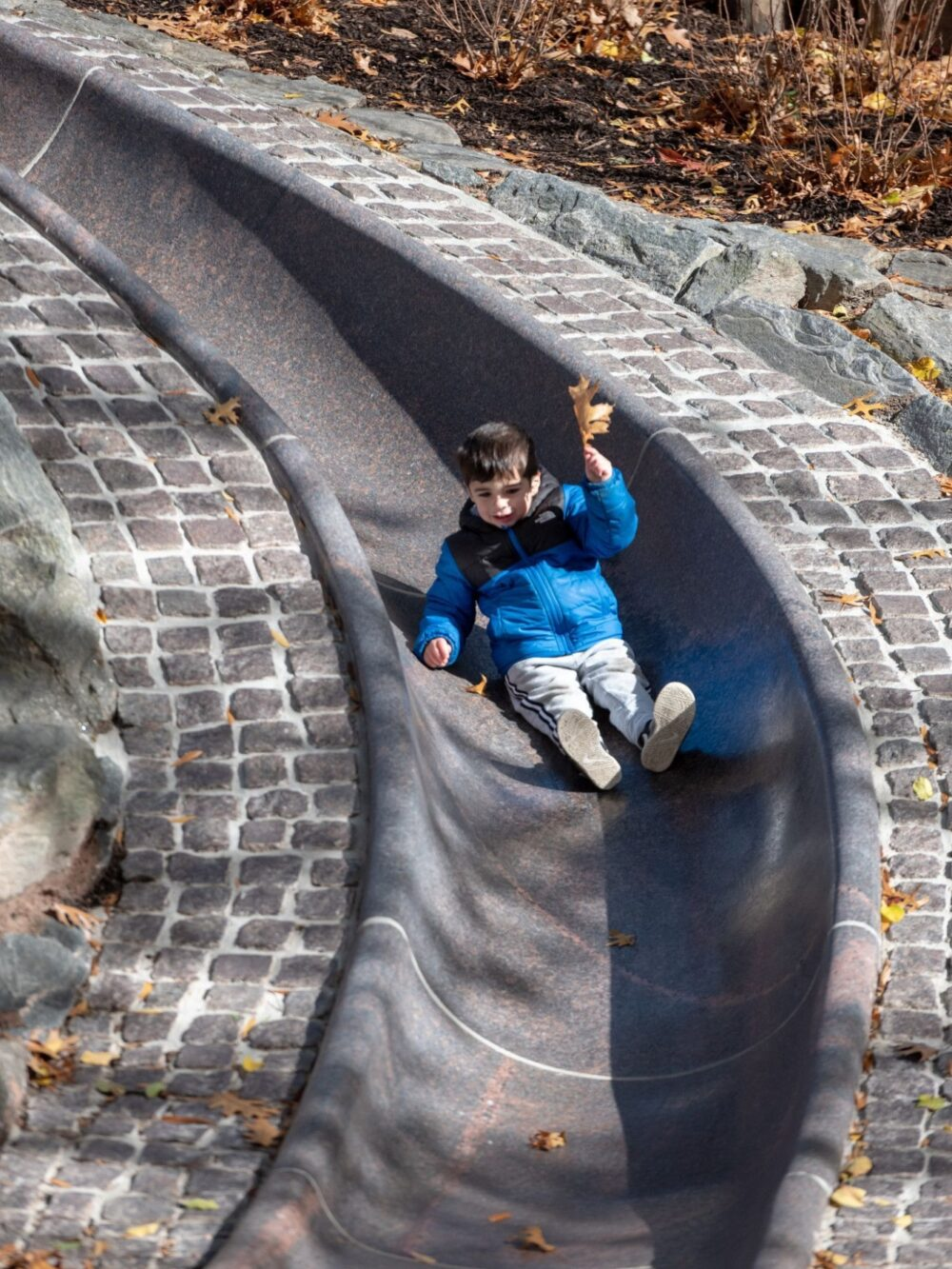 A young boy slips down the long, curving sliding pond