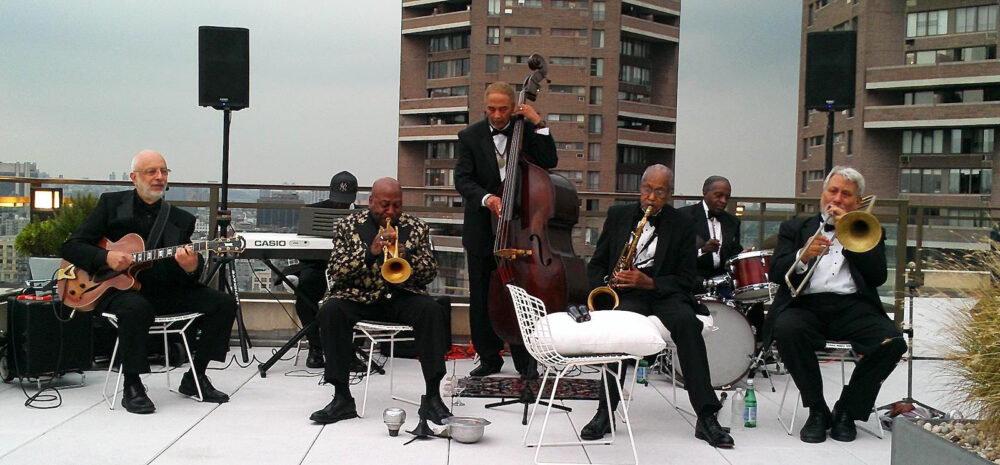 The band is pictured playing in formalwear on a Harlem rooftop.