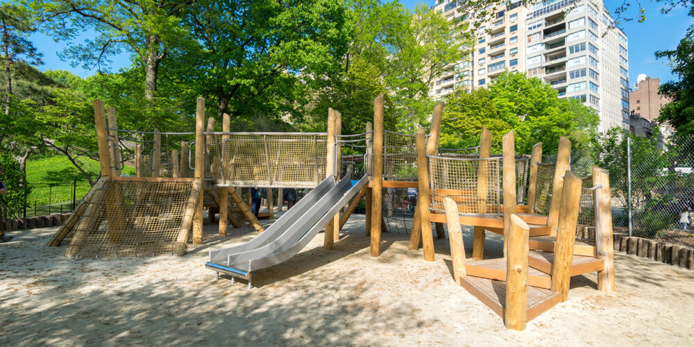 Play apparatus made of wood and rope on a sandy lot, shaded by trees