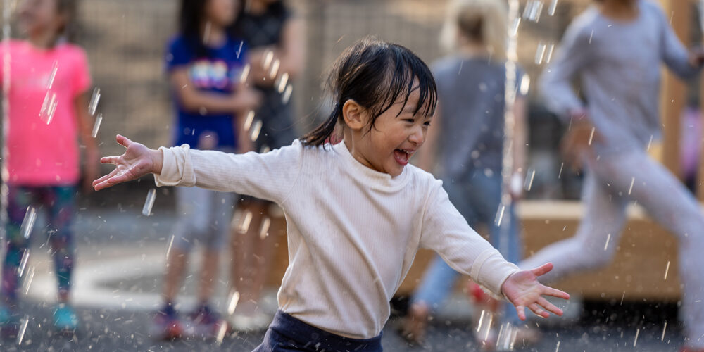 A young girl enjoys running through the spray of a water feature