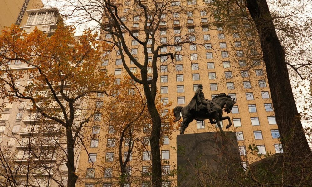 Looking out from the Park across 57th Street, the statue is seen in profile against a building.