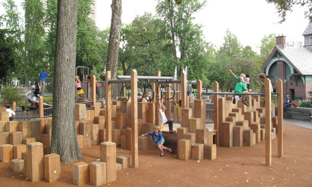 Children climbing the wood pilings and climbing rings of the playground.