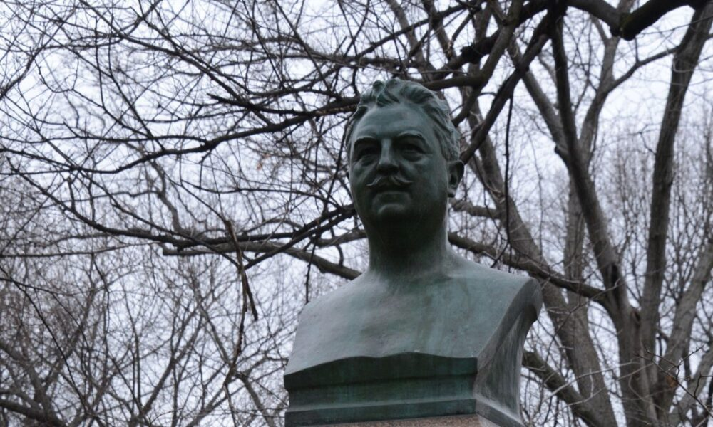 The bust is framed by a background of bare, winter branches
