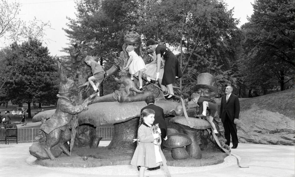 Historical photo of kids climbing on the Alice in Wonderland statue