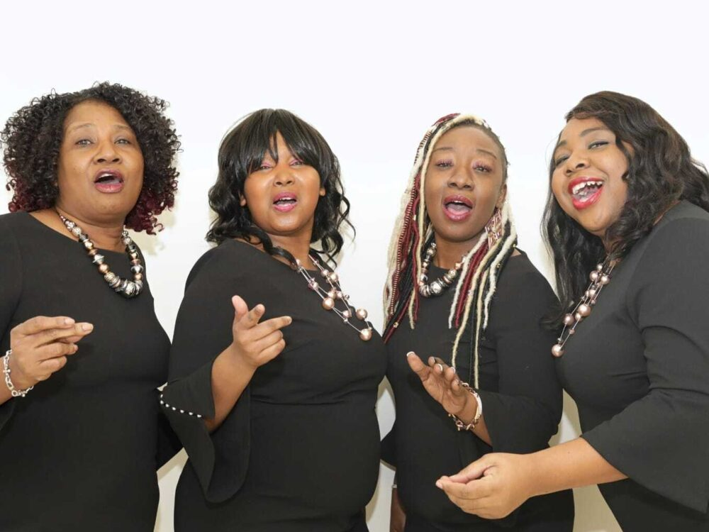The quartet is captured mid-song against a white backdrop.
