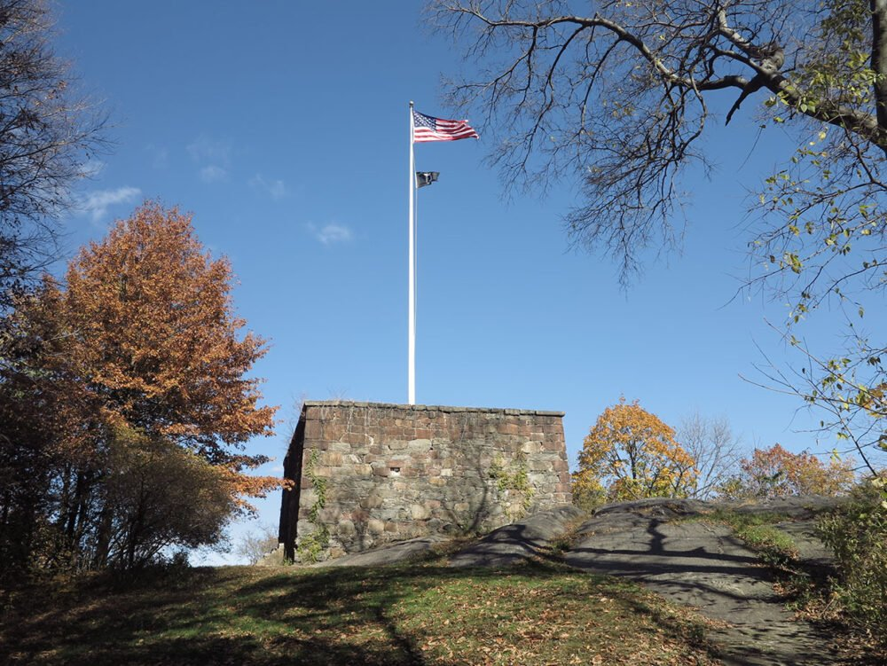 The flag of the United States flies high on the flagpole of the Blockhouse