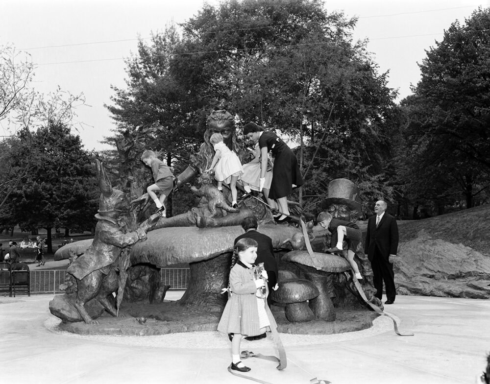 Robert Moses stands to one side, enjoying the children clamboring over the statue
