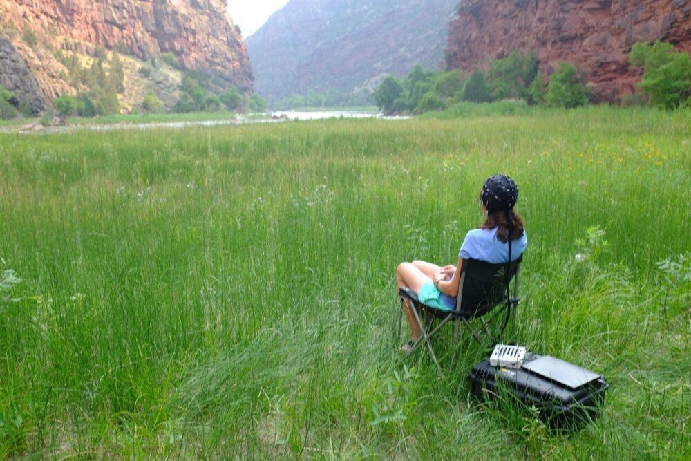 A woman wearing brain-scanning apparatus sits in a mountain glen