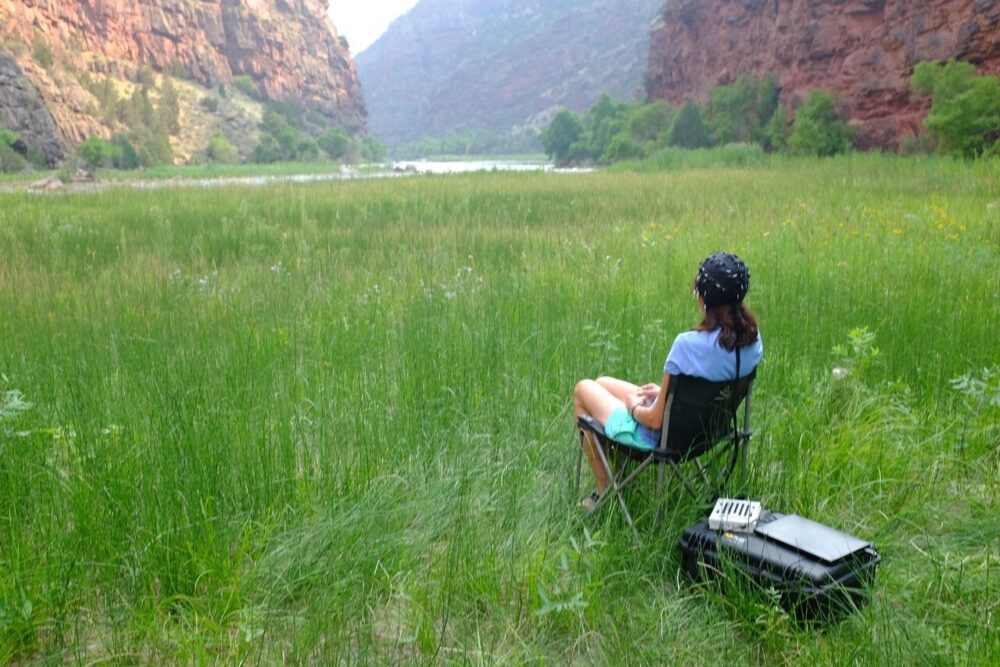 A woman wearing brain-scanning apparatus sits in a mountain glen