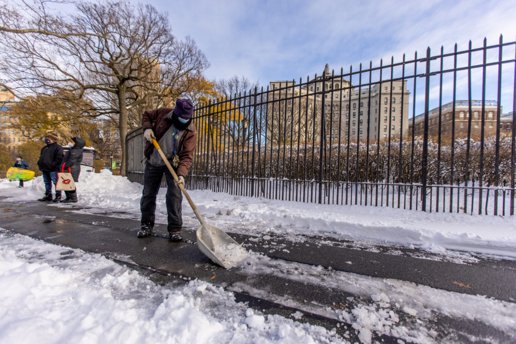 A conservancy staff member clears a path of snow on a bright winter day