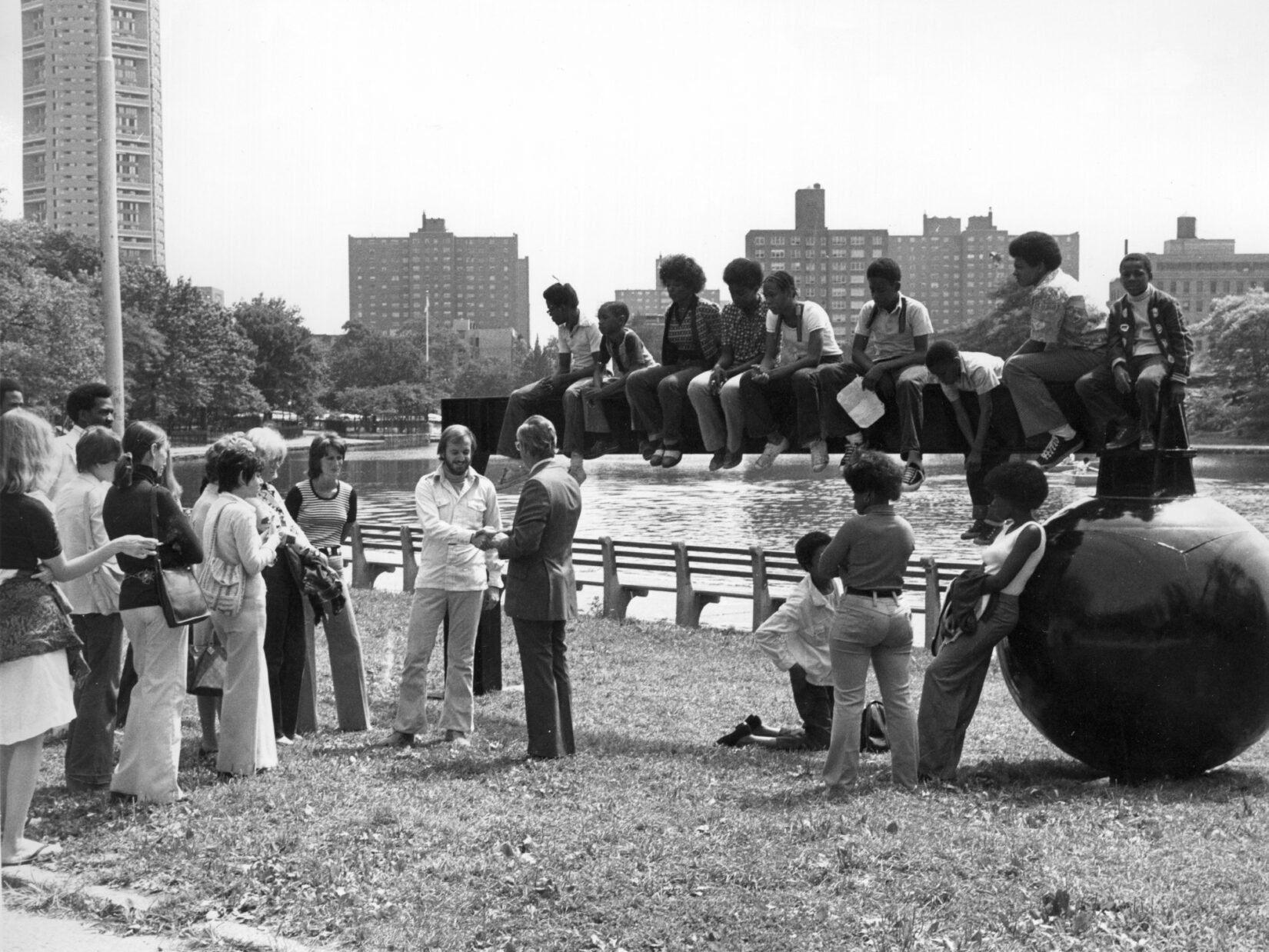 A black and white photo of the sculpture on the banks of the Meer, with people surrounding and sitting on top of it.