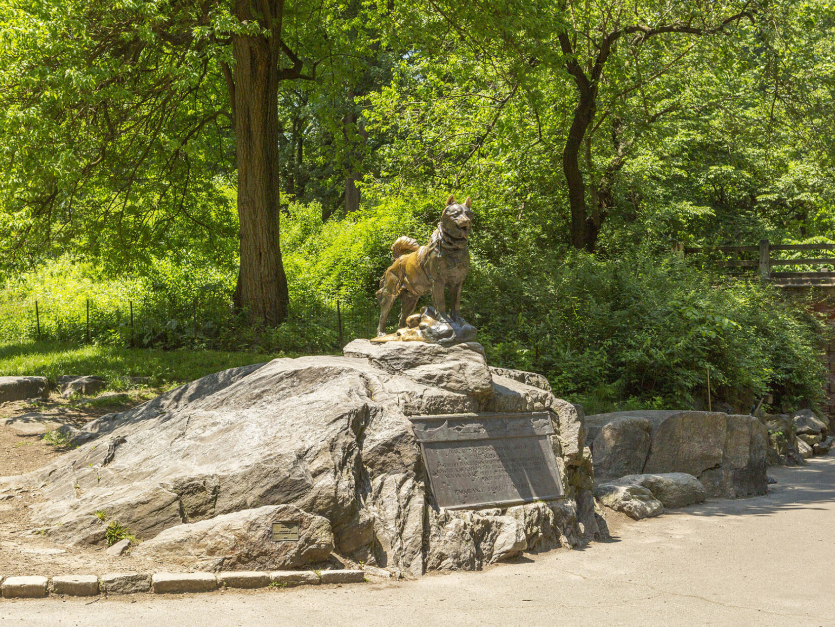 Balto is seen standing proudly on his rock, above the accompanying plaque, on a sunny day