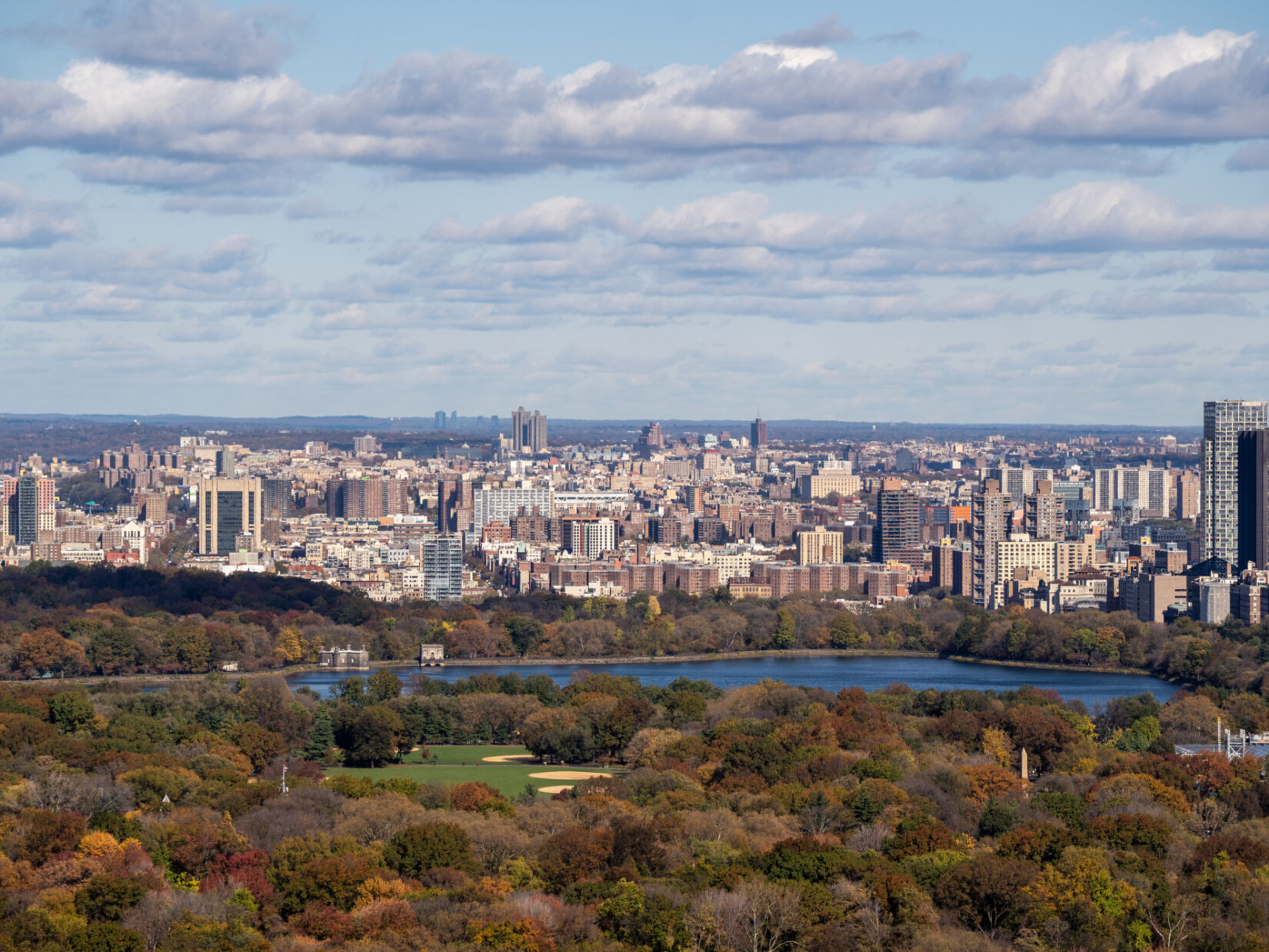 An aerial view looking north from the end of the Great Lawn, past the Reservoir, to the skyline of Harlem in the background