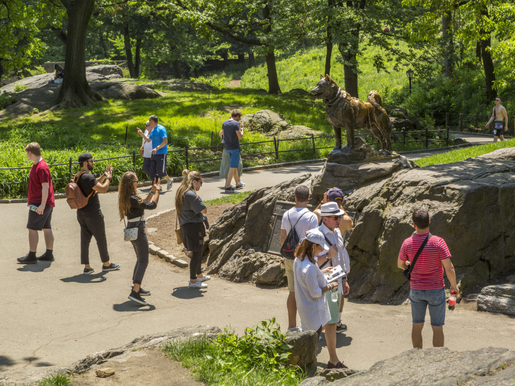 Visitors admire and photograph the statue of Balto on a sunny day