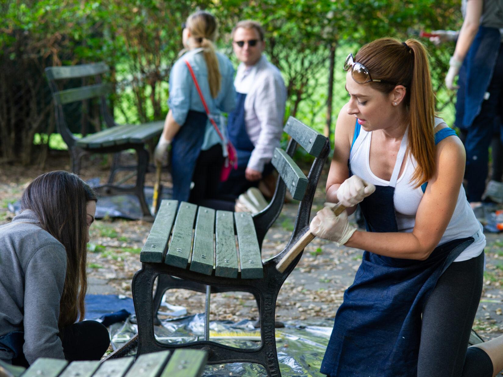 Seasonal volunteers help out refurbishing park benches