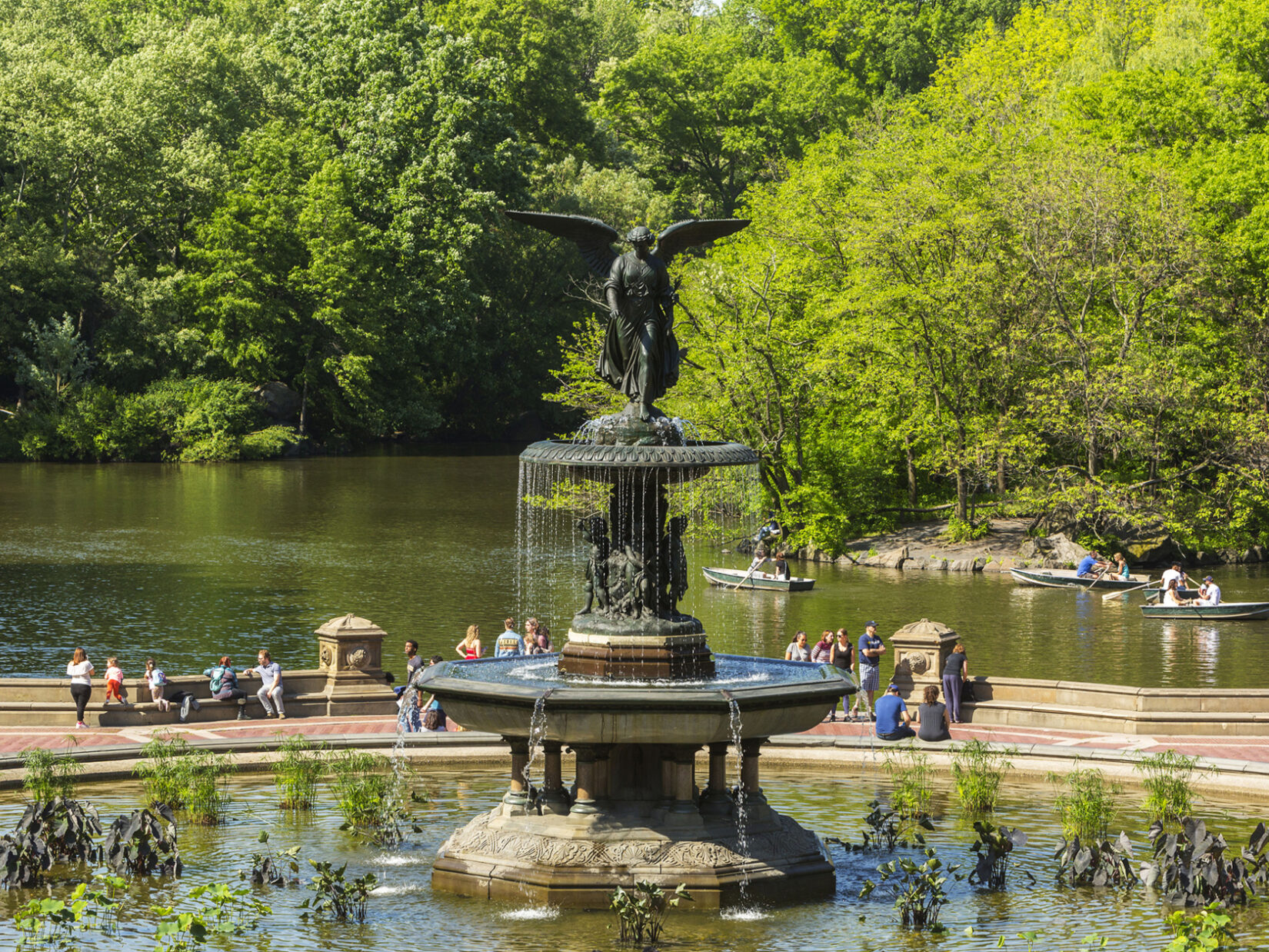 Bethesda Fountain with parkgoers behind it and boaters on the Lake behind them