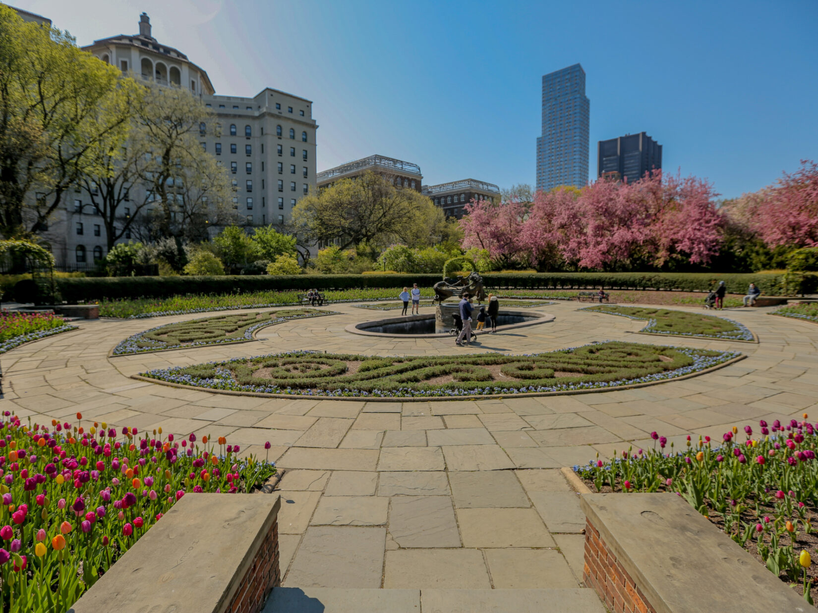 A section of Conservatory Garden pictured under a cloudless blue sky, showing the early blooms of spring.