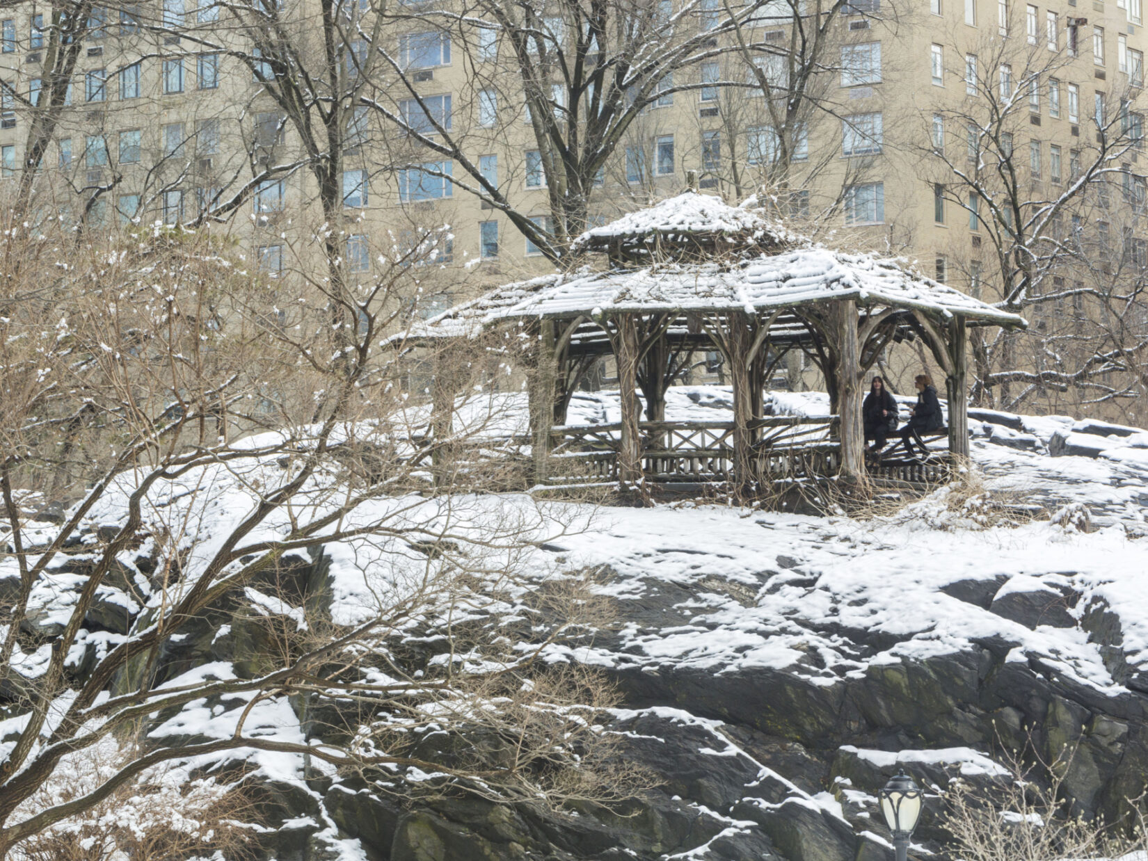 The Shelter is pictured dusted with snow with two parkgoers enjoying its shelter