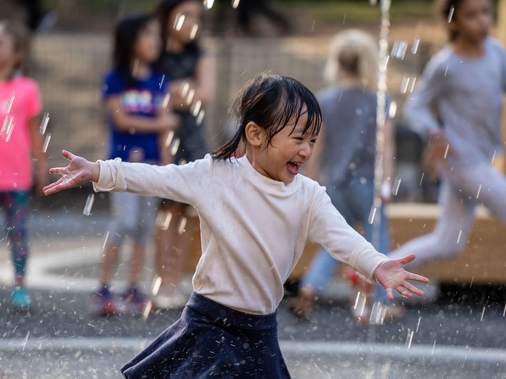 A young girl runs joyfully through the spray of a fountain