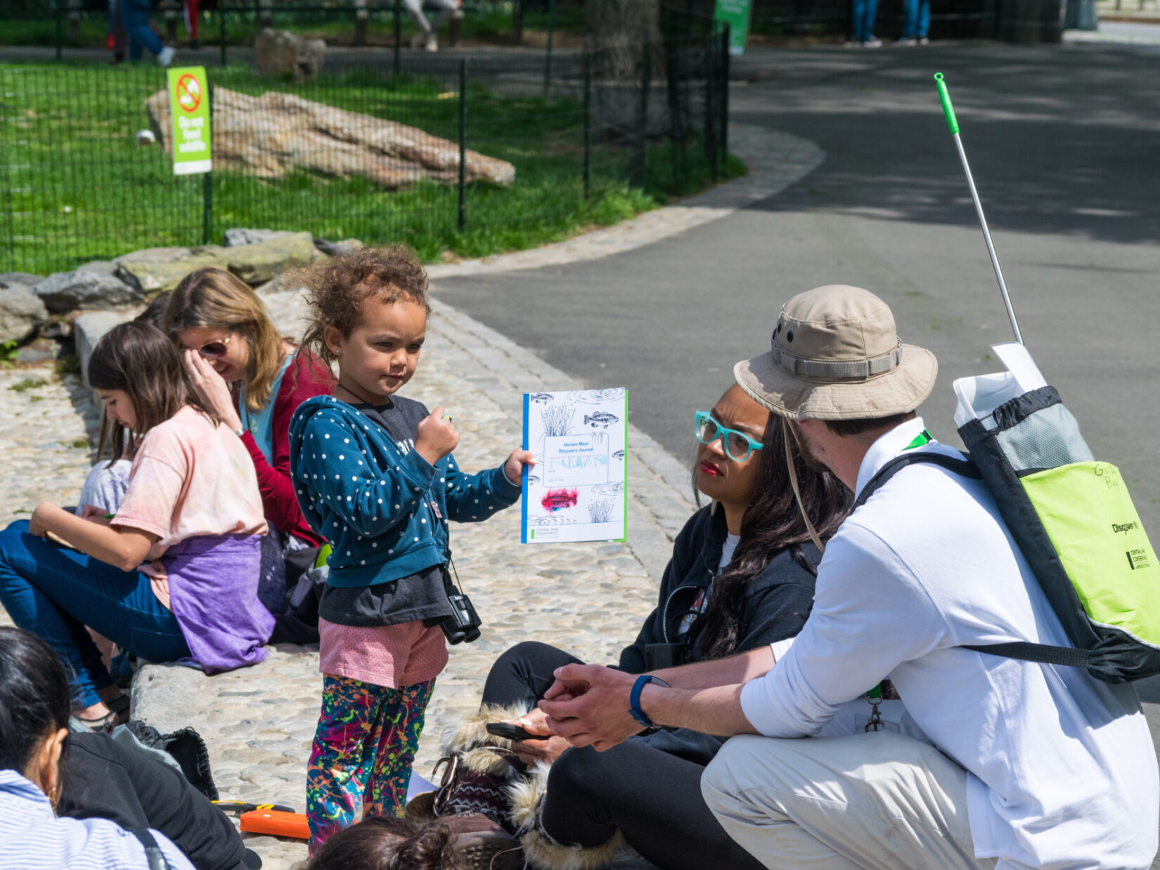 A young girl shows her work to a Park guide
