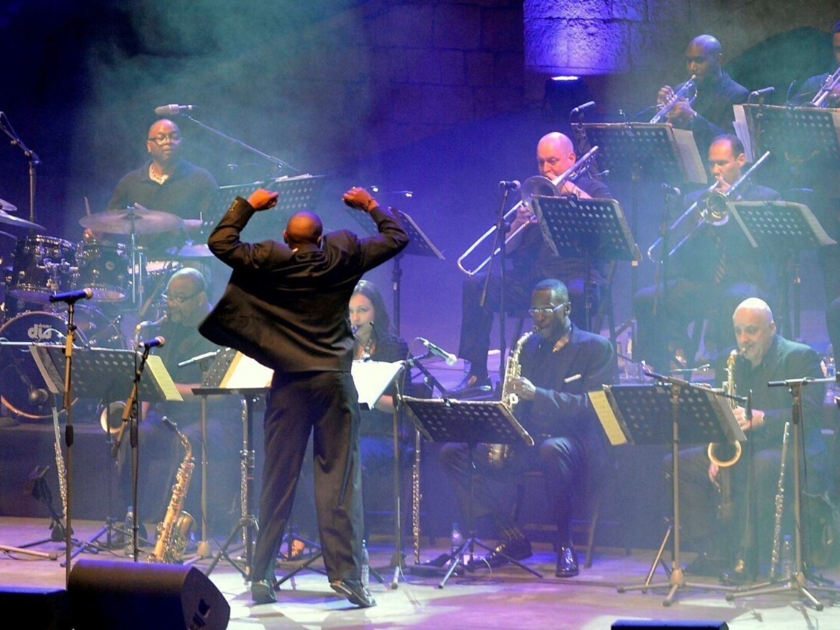 The conductor's arms are over his head while the big band wails.