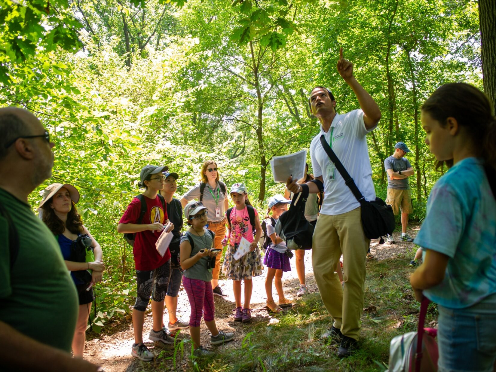 Kids and tour-goers in rapt attention to a tour guide in the North Woods