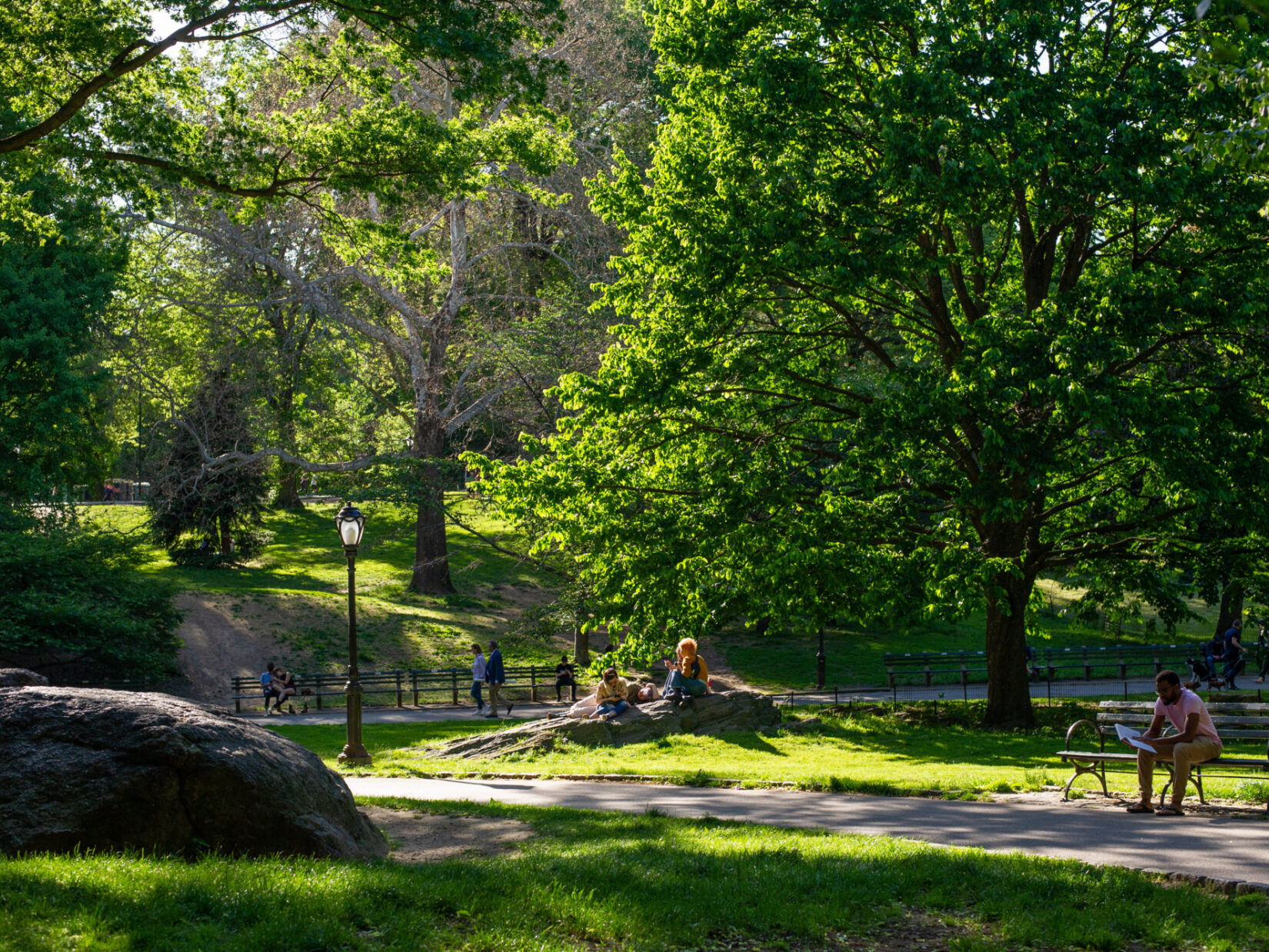 Parkgoers perch on outcroppings and benches on the path along the Great Lawn