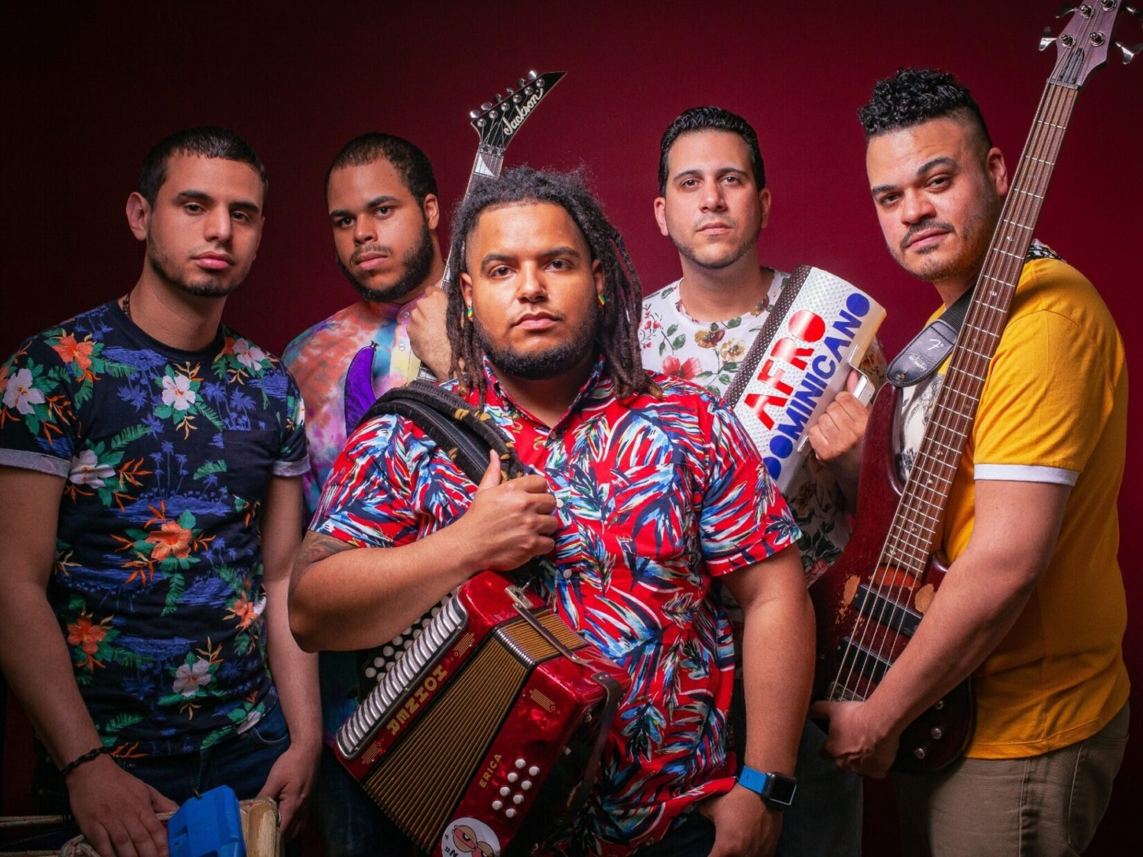 Members of the band pictured with their instruments against a red backdrop.