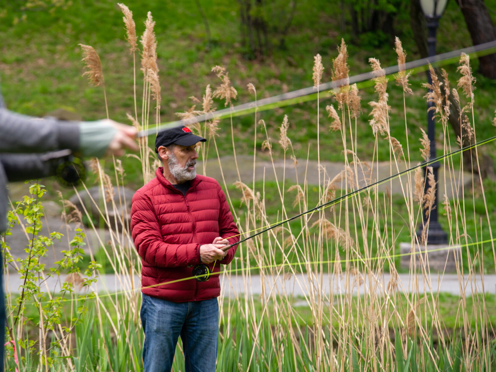 Two fishermen, dressed for chilly weather, casting their fishing rods on the Harlem Meer