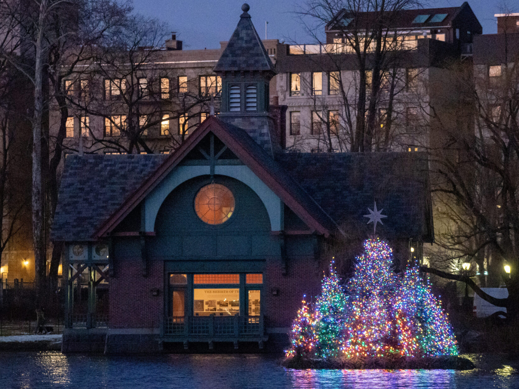 The Charles A. Dana Discovery Center is the evening backdrop for a small island of colorfully lit holiday trees