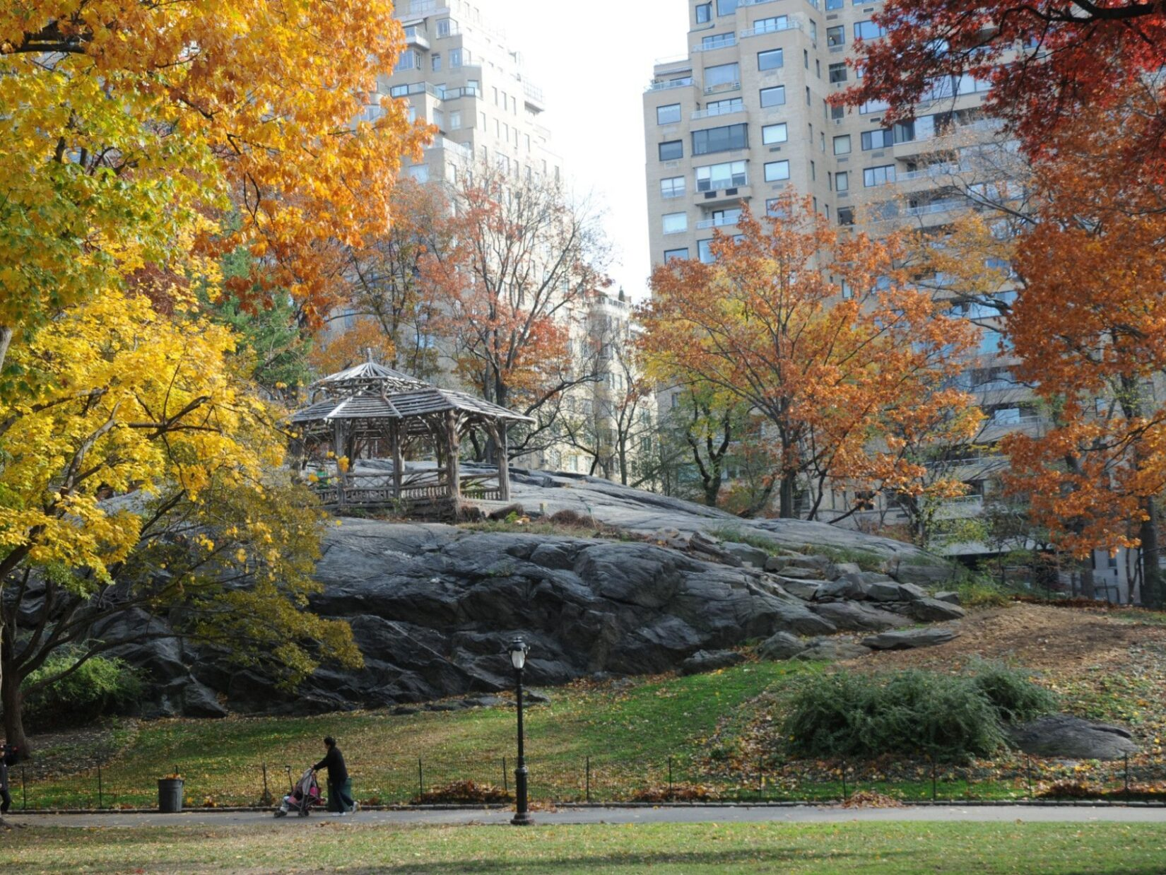 A rustic structure perches atop a large schist outcropping surrounded by fall trees