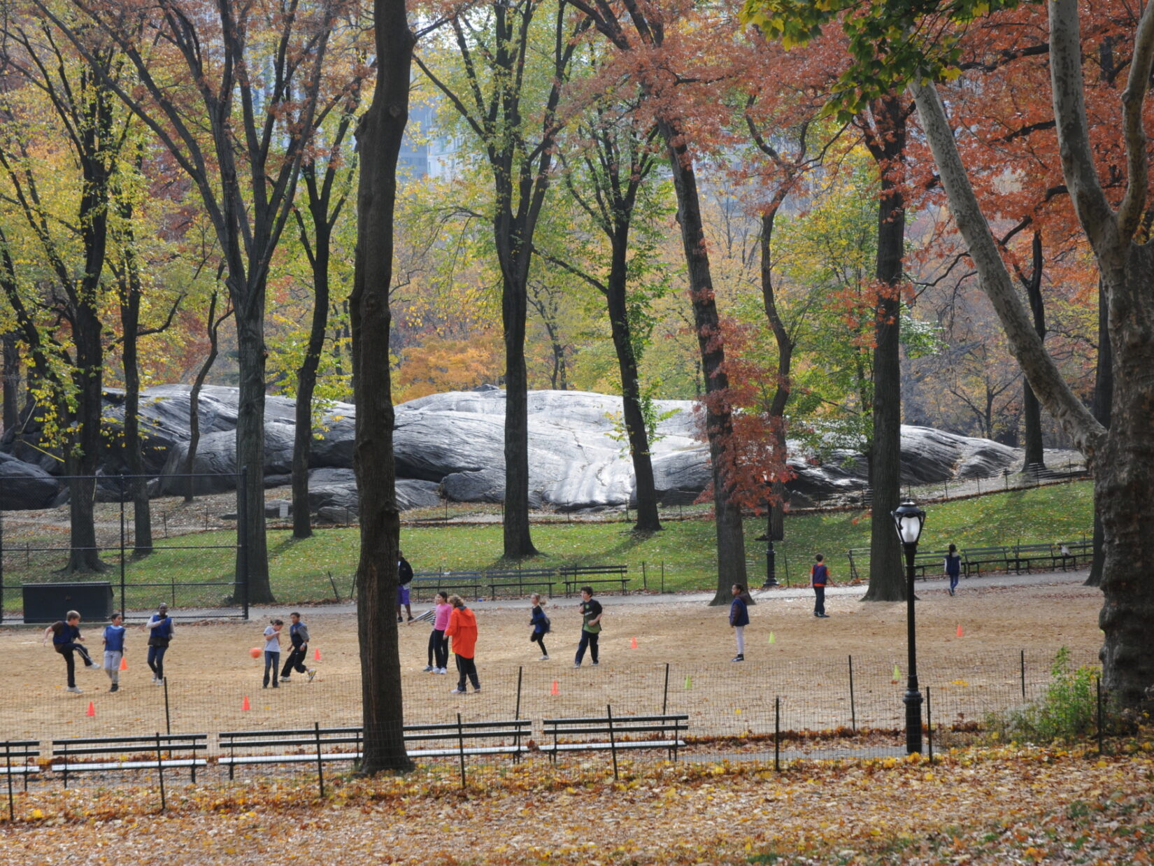 An autumn scene of a group of children playing at Heckscher Ballfield