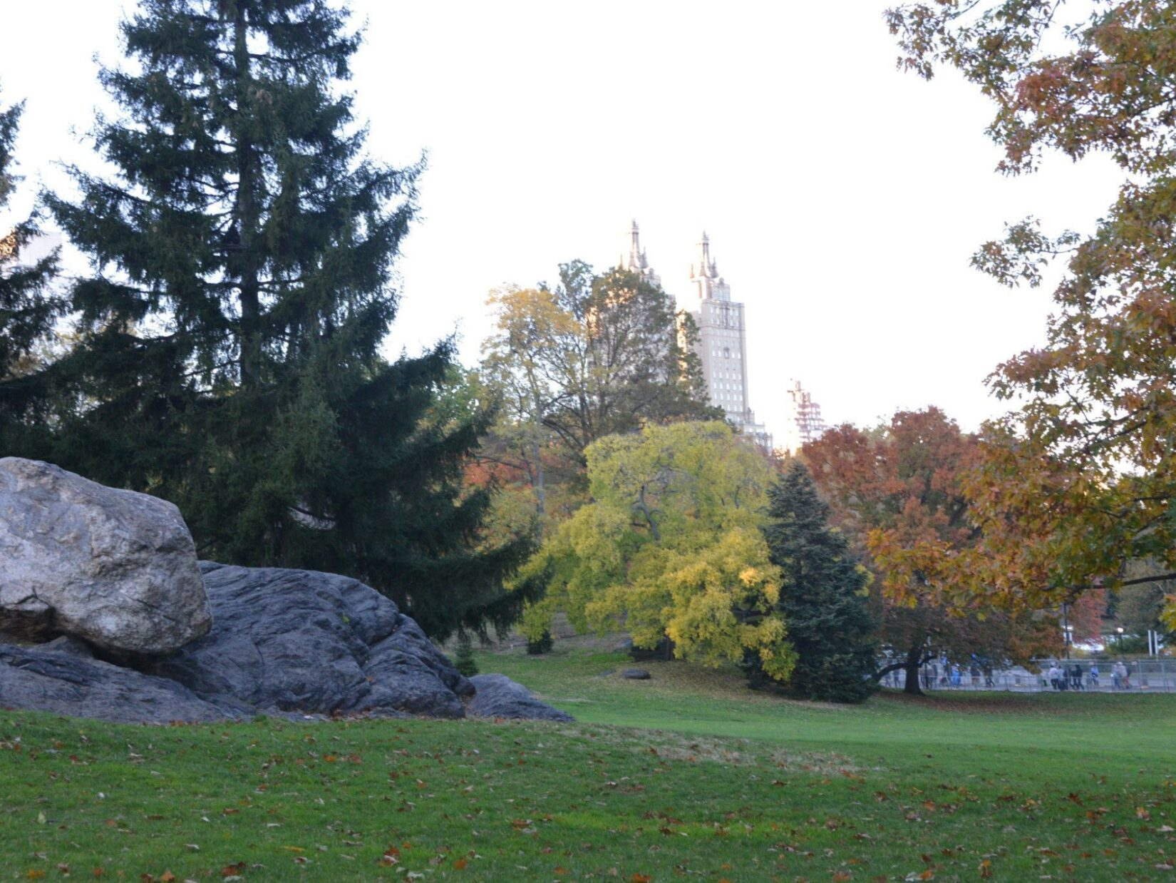 The landscape is shown featuring schist and pines surrounding a green lawn.