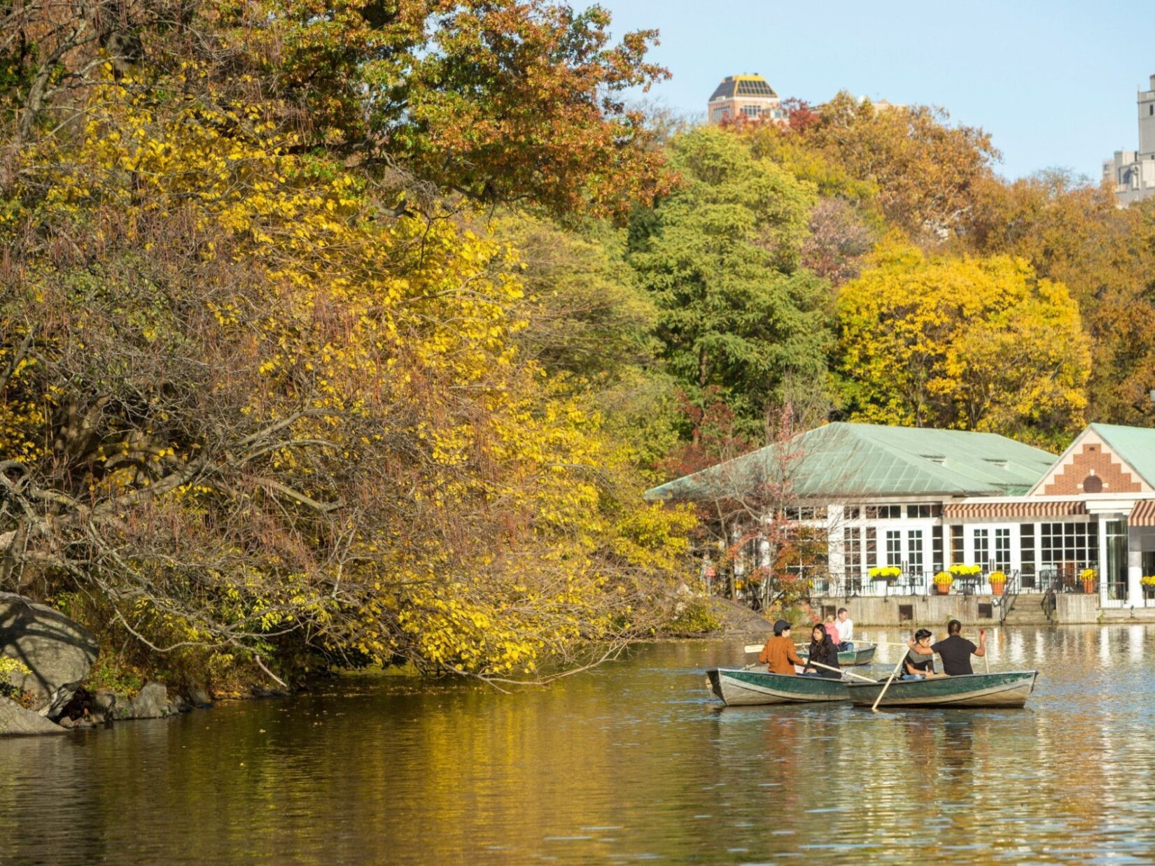 The Loeb Boathouse is seen at the far end of the Lake, behind boaters and the trees on the banks.