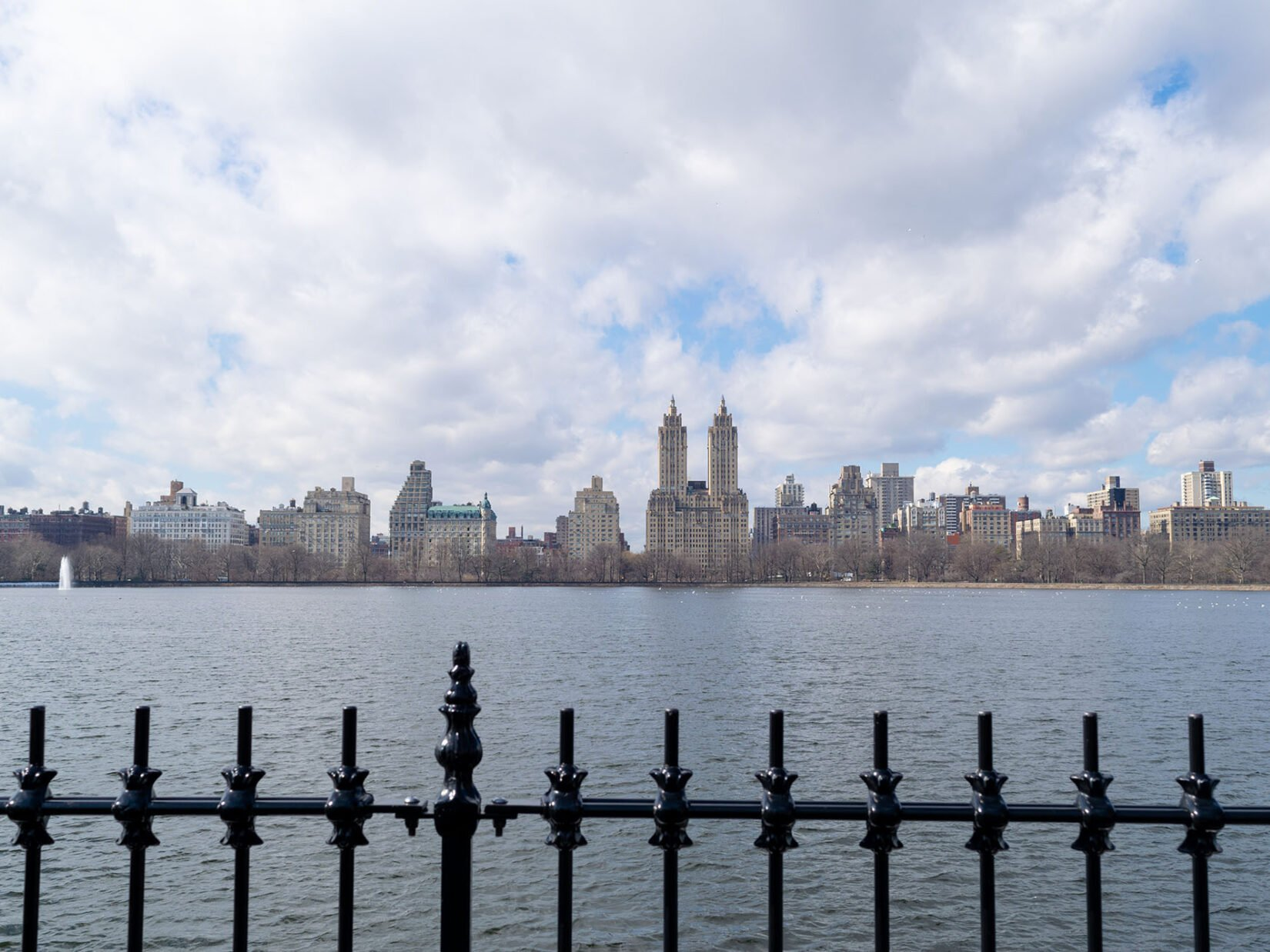 Looking across the Reservoir on a cloudy day with the ironwork of the fence in the foreground