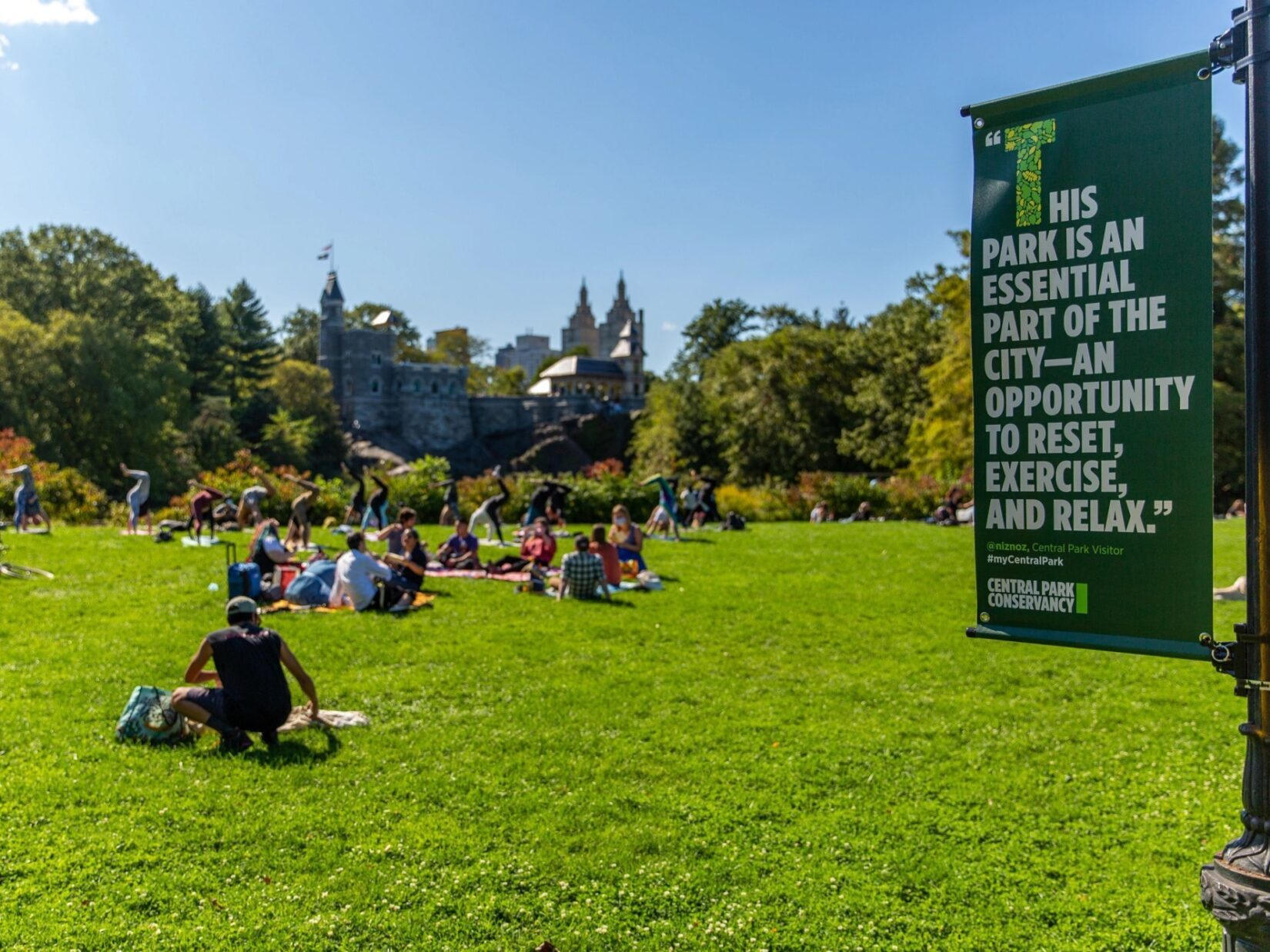 People enjoy a Park lawn under a beautiful blue sky, with a banner hanging from a lamppost entering the frame on the right. The banner has a quote about the Park.