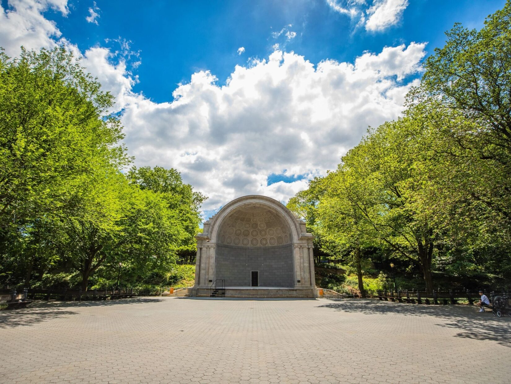 The bandshell is seen from across an empty plaza on a sunlit sping morning
