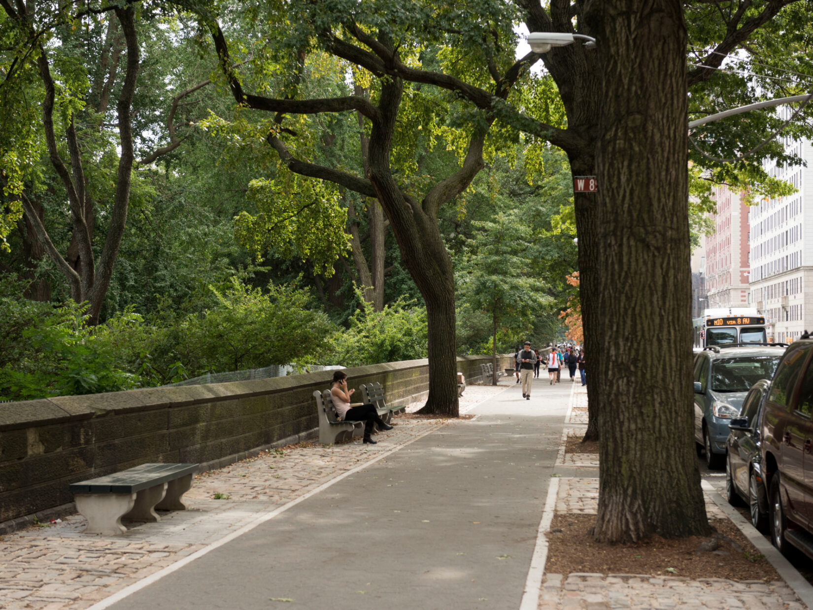 A view of the perimeter in summer, with pedestrians in the distance, one of them sitting on a park bench.