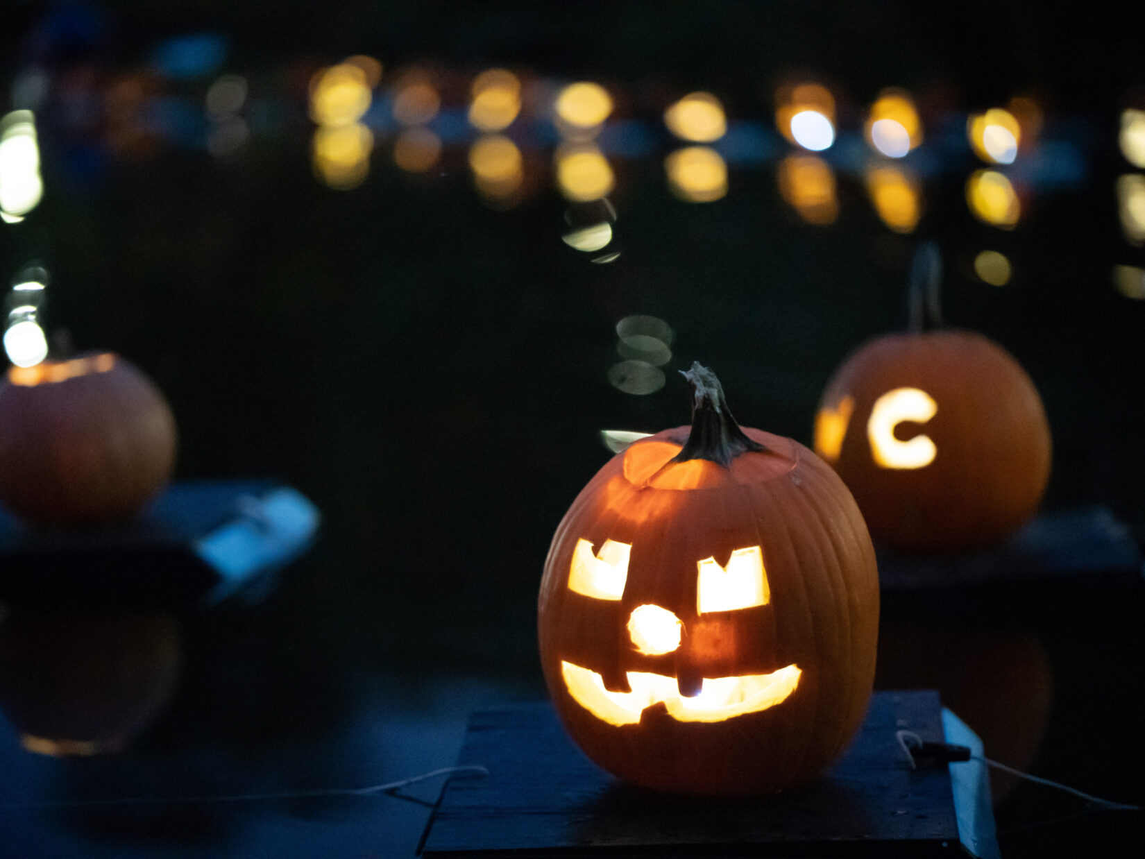 Pumpkins, lit from within, floating on the Harlem Meer at night