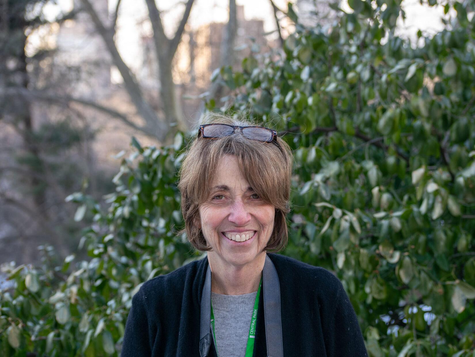Portrait image of Sara Cedar Miller, seen in front of Park greenery