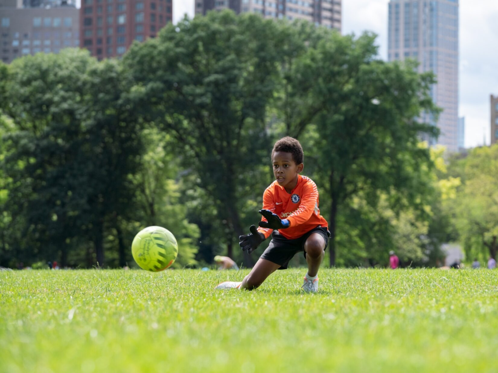A young goalie keeps his eye on the ball on the North Meadow with the skyline in the background