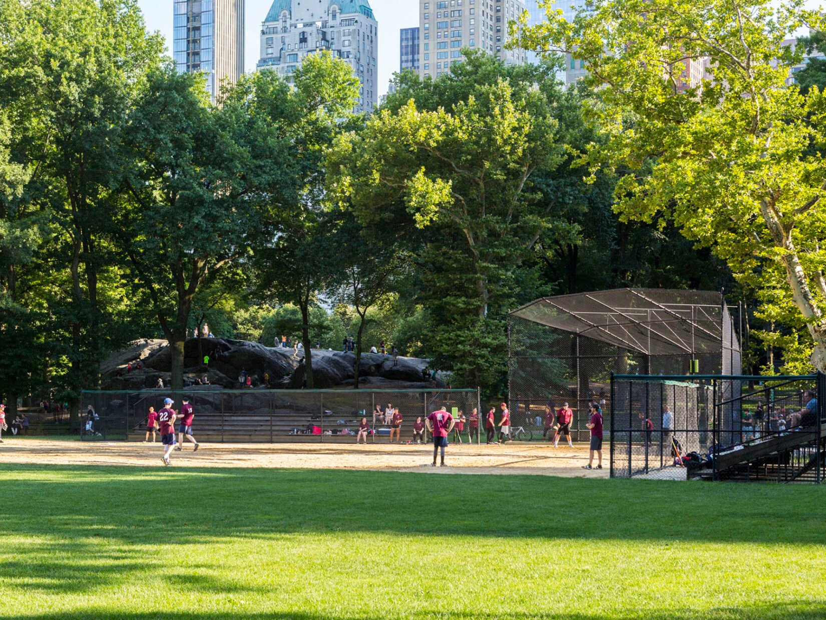 A summer softball game on Heckscher Ballfields with Umpire Rock looming in the background