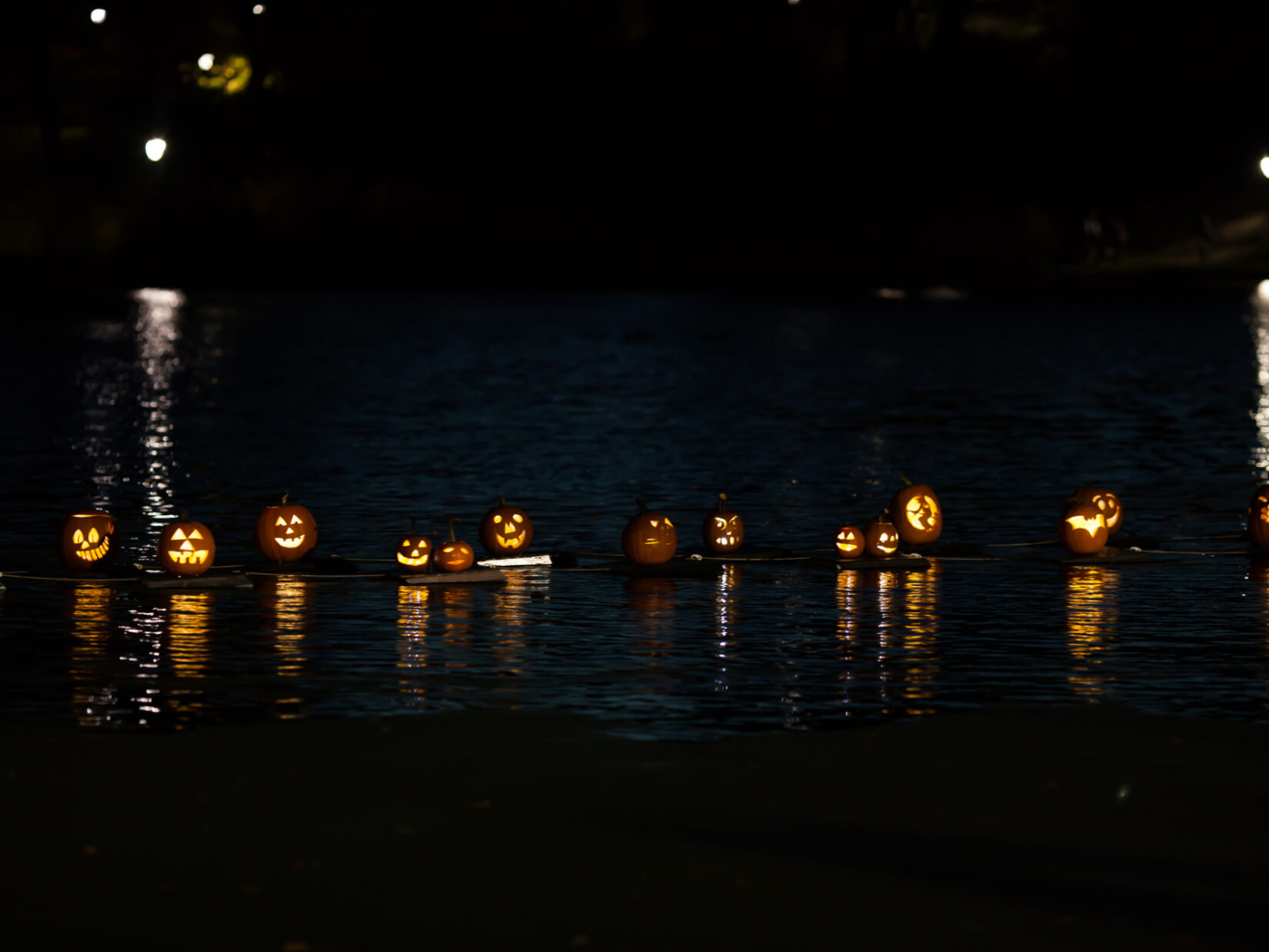 Pumpkins, lit from within, floating on the Meer at night