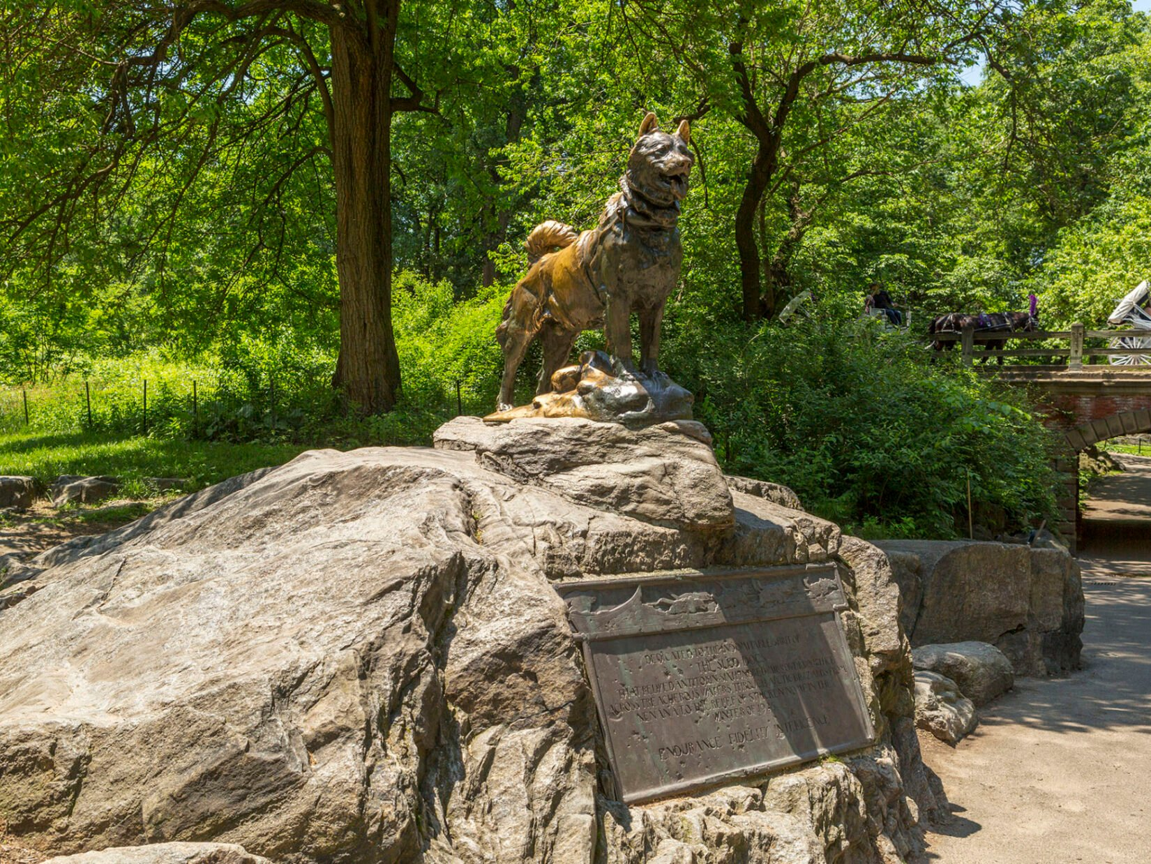A photograph of the statue perched on an outcropping and the accompanying plaque