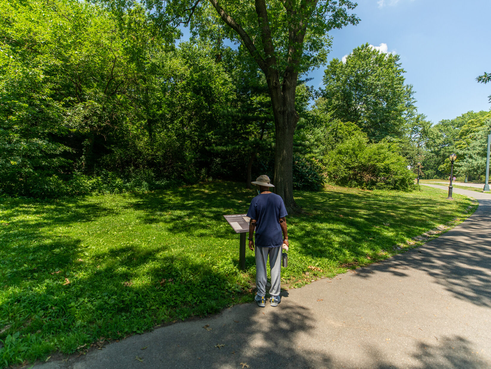 Park visitor reading Discover Seneca Village signage