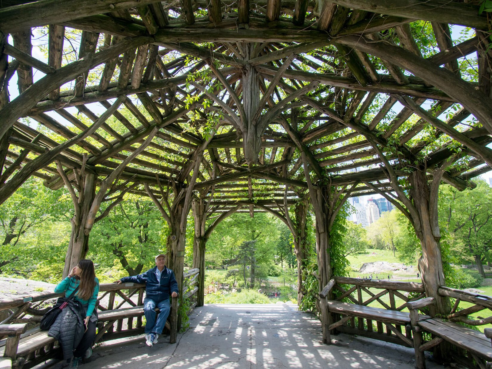 The roof of the rustic structure is a dramatic frame for two visitors seated below