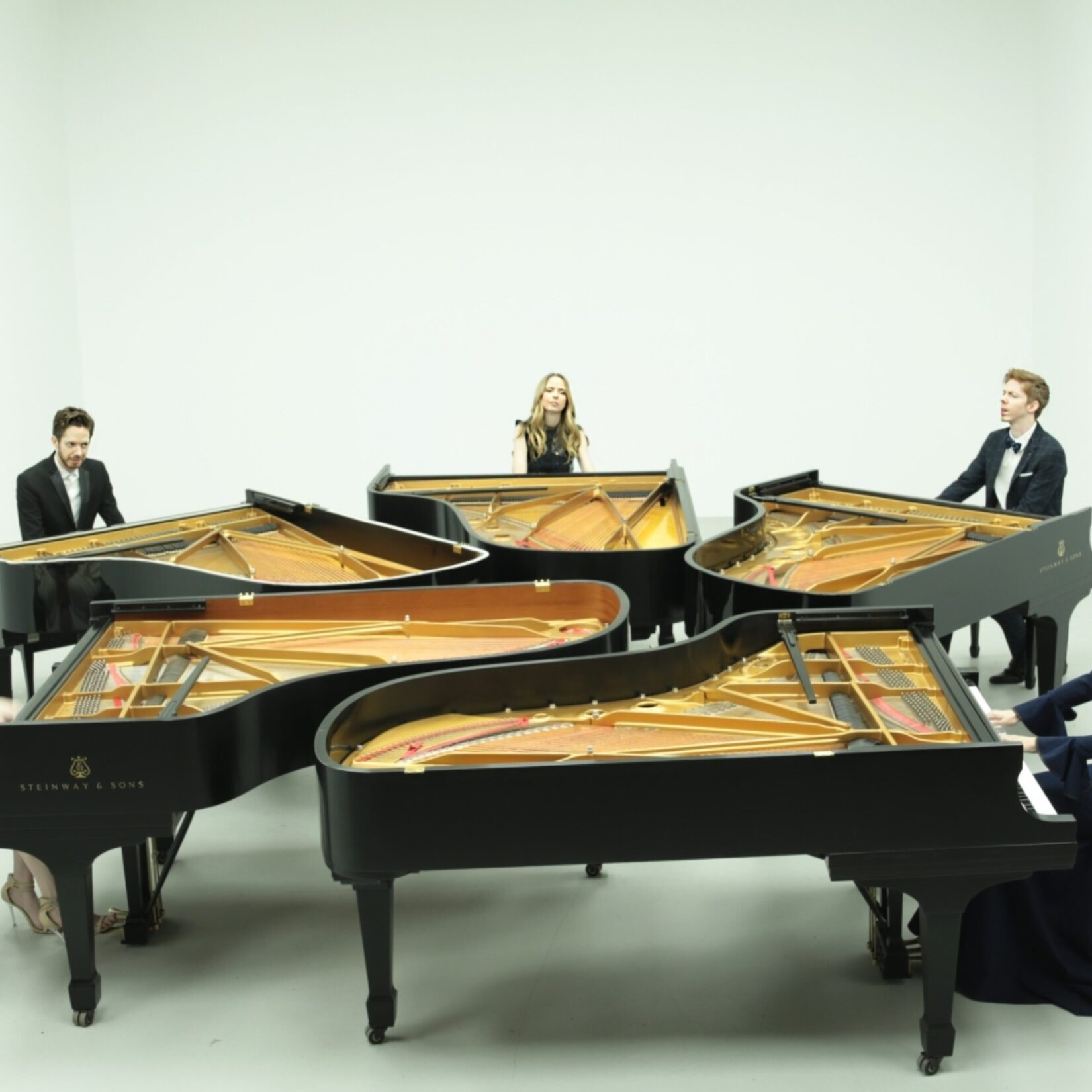 Five grand pianos are clustered together so the pianists form a semi-circle