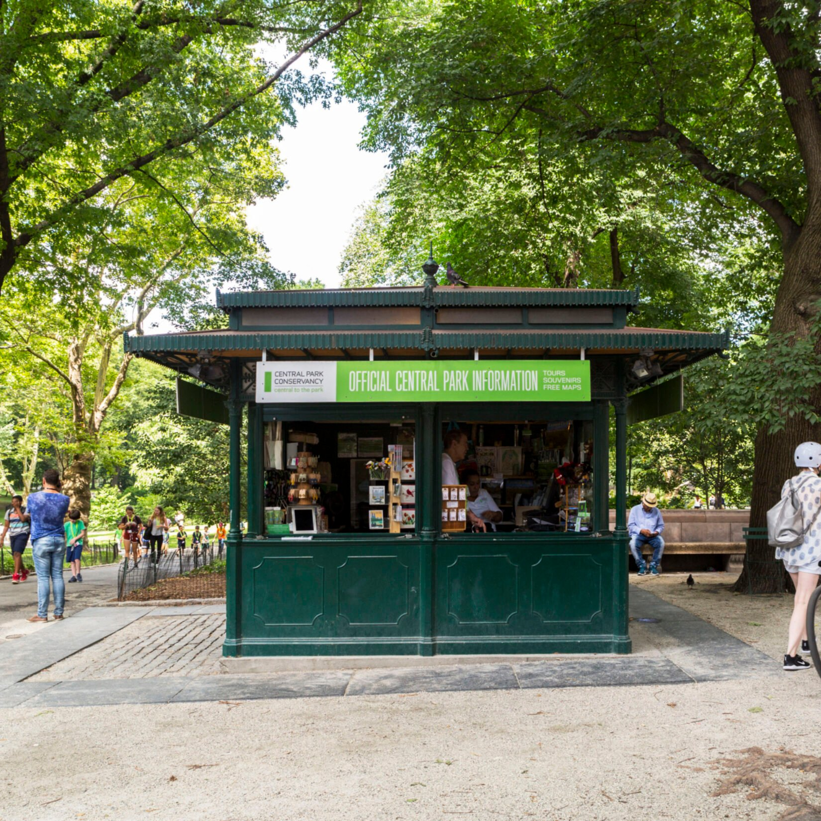 The kiosk is seen framed by summer trees and passing pedestrians.