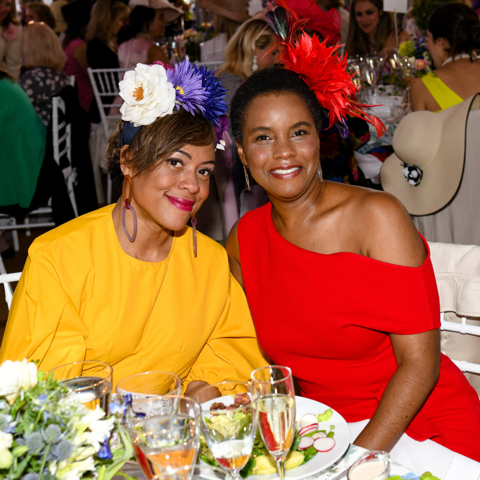 Two women sporting flowered hats enjoy the luncheon