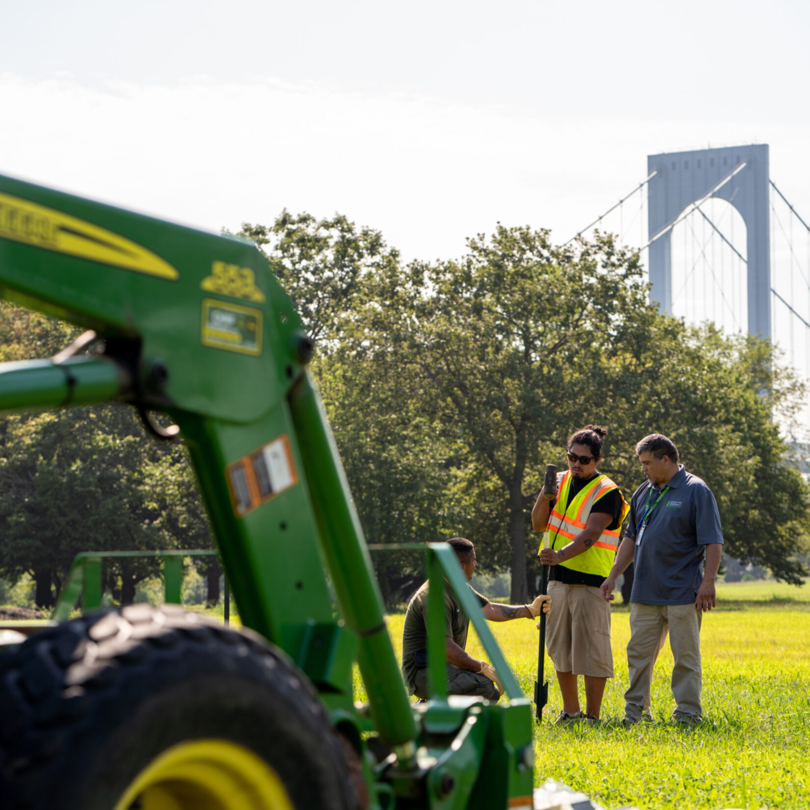 Park staff working at Ferry Point Park, with the Throgs Neck Bridge in the distance